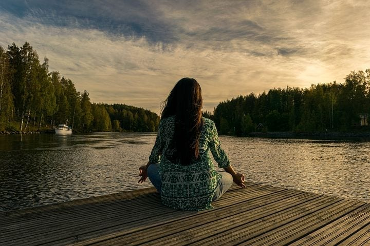 woman meditating on dock with migraine & anxiety