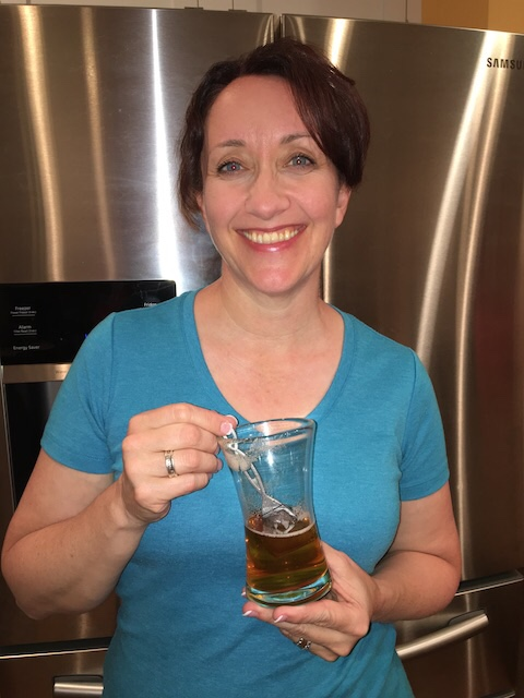 woman in blue shirt with glass of beer using PureWine The Wand to prevent migraine