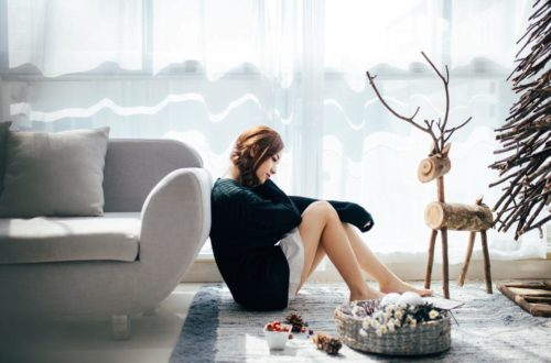 woman sitting by couch having negative feeling at the holidays