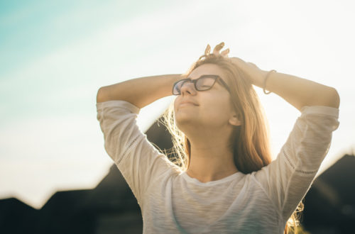 A girl with her hands over her head looking at the sky
