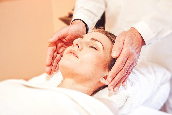Woman getting a chiropractic adjustment from a chiropractor to relieve migraine