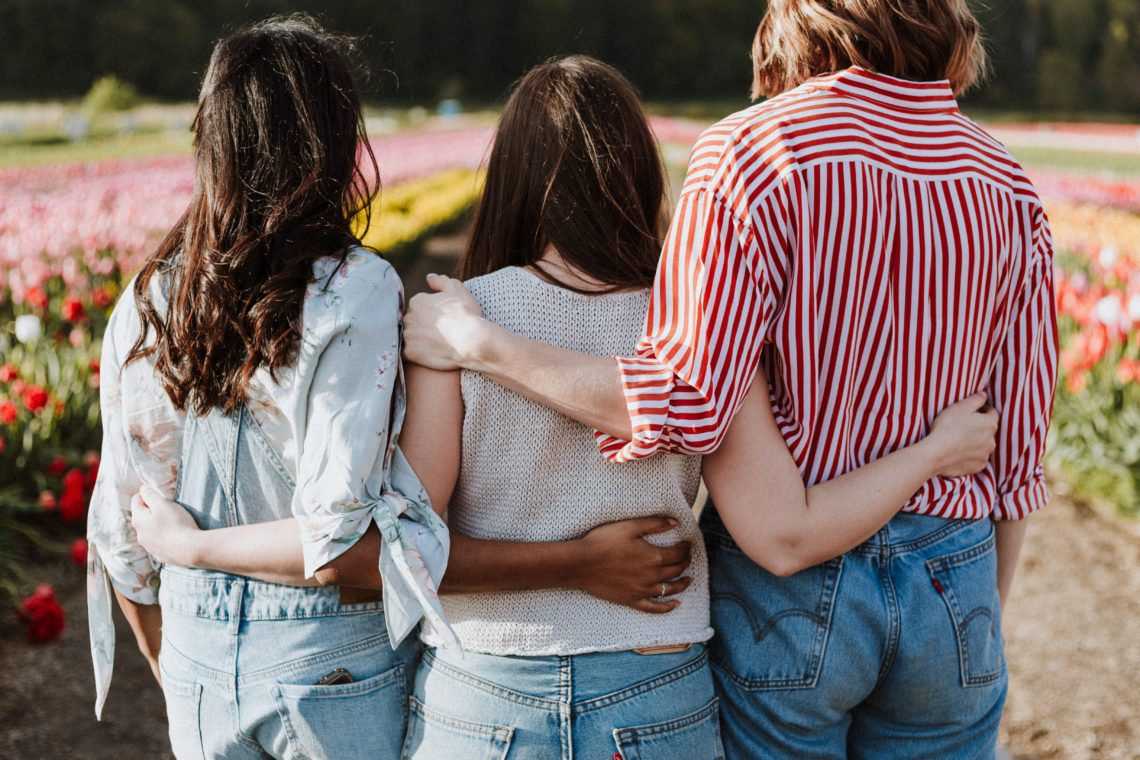 People linking arms standing in support