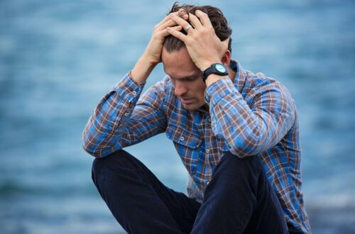 man grasping his head experiencing different types of migraine