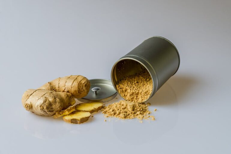 ginger root and a silver container on its side spilling ginger powder