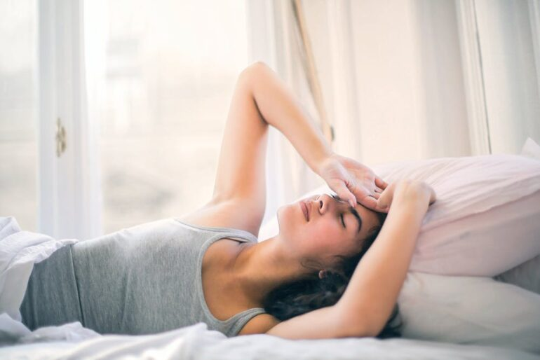 woman lying in bed with migraine and fatigue