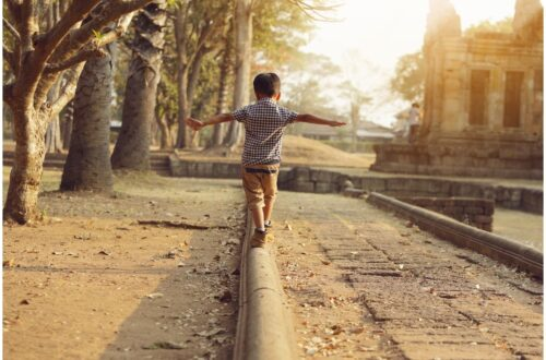 boy walking on log withe arms outstretched for vestibular rehab therapy